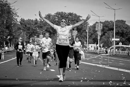 September 15, 2019 Minsk Belarus In black and white, a happy woman running a marathon celebrates with a show of hands