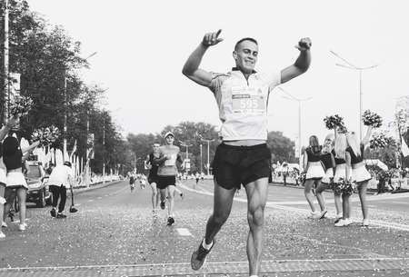 September 9, 2018 Minsk Belarus In the black-and-white image, a participant celebrates with his hands raised as he crosses the finish line of the marathon 新聞圖片