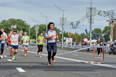 September 15, 2019 Minsk Belarus A happy woman runs to the finish line of the marathon ahead of happy athletes
