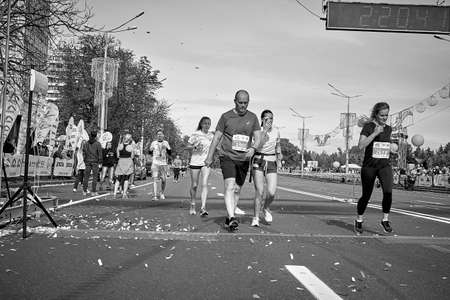 September 15, 2019 Minsk Belarus In the black and white version of the marathon race, active marathon runners cross the finish line on a city road Éditoriale