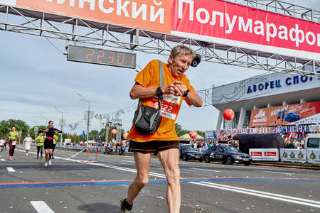 September 15, 2019 Minsk Belarus A mature participant has crossed the finish line of a marathon and checks the heart rate monitor on his smart watch