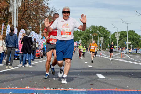 September 15, 2019 Minsk Belarus A marathon race in which a Mature athlete with raised hands runs to the finish line on a city road Éditoriale