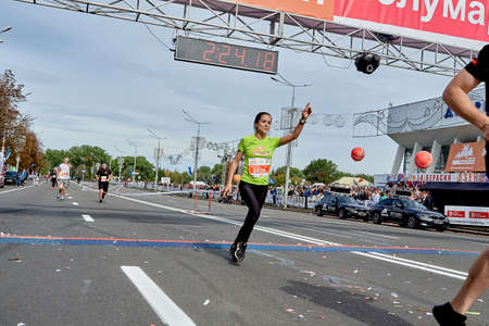 September 15, 2019 Minsk Belarus A marathon race in which an active, happy woman crosses the finish line of a marathon with her hand raised Éditoriale