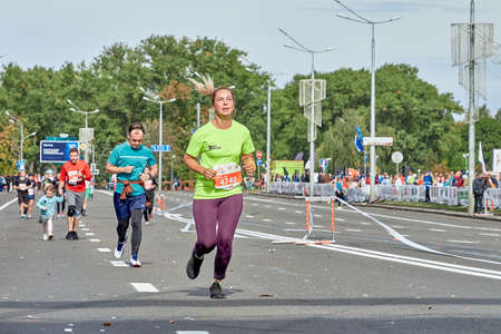 September 15, 2019 Minsk Belarus A marathon race in which an active woman in a green shirt runs to the finish line of the marathon