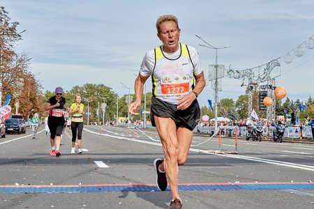 September 15, 2019 Minsk Belarus A Mature strong athlete crosses the finish line of a marathon Editorial