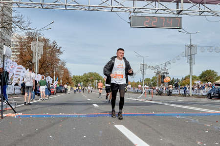 September 15, 2019 Minsk Belarus A marathon race in which a happy athlete with a smartphone in his hand crosses the finish line of the marathon.