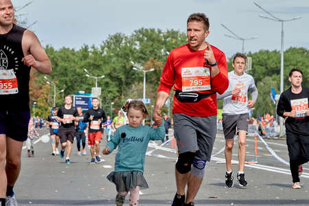 September 15, 2019 Minsk Belarus Close-up of an emotional father and daughter running a marathon on a city road among a group of athletes