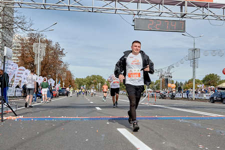 September 15, 2019 Minsk Belarus A marathon race in which a happy athlete with a smartphone in hand crossed the finish line Éditoriale