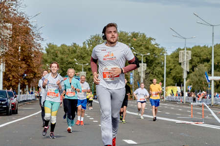 September 15, 2019 Minsk Belarus A marathon race in which an active participant with headphones runs among a group of participants on a city road