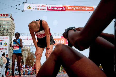 September 15, 2018 Minsk Belarus Half Marathon Minsk 2019 Tired athlete bowed his head resting before a tired woman athlete sitting on the pavement