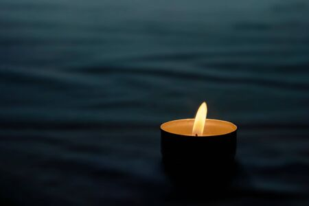 In memory of the victims, a candle is lit on a black background.Memorial day