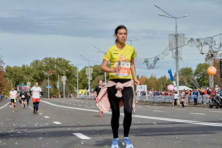 September 15, 2019 Minsk Belarus A young woman with a phone in her hand runs along the city road of the Minsk half marathon