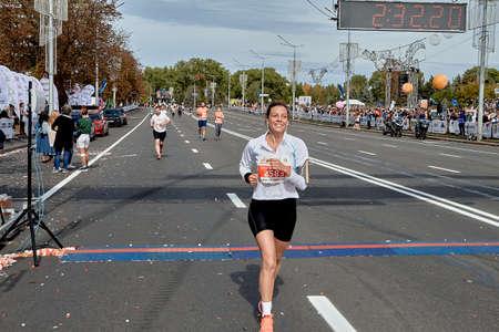 September 15, 2019 Minsk Belarus A happy woman crosses the finish line on the city road of the half marathon in Minsk
