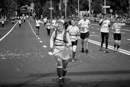 September 15, 2019 Minsk Belarus In black and white, an active, happy woman runs a city road marathon Editorial