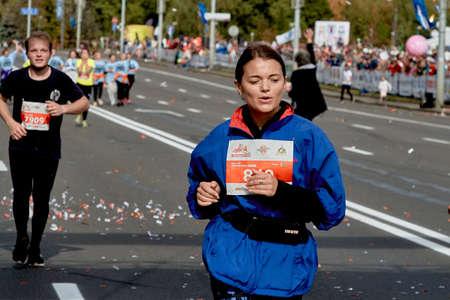 September 15, 2019 Minsk Belarus Close up of a young woman in a blue jacket running a marathon