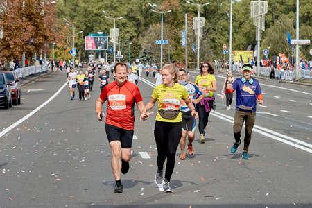 September 15, 2019 Minsk Belarus A couple of marathon runners run hand in hand along a city road