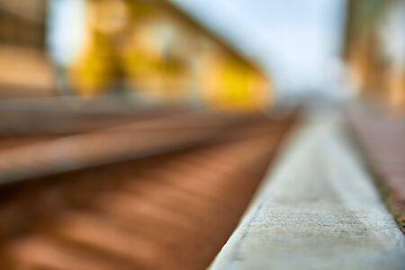 Close-up of a railway platform and rails. Railway station in blur.Shallow depth of field. Reklamní fotografie