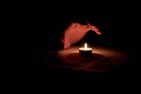 A human hand over a burning candle in honor of the commemoration