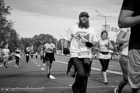 September 15, 2019 Minsk Belarus In black and white image,an athlete with a beard crosses the finish line among the competitors Editorial