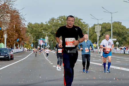 September 15, 2019 Minsk Belarus A marathon race in which a Mature participant in glasses runs ahead of other athletes