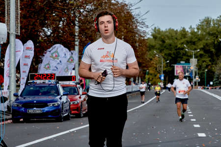 September 15, 2019 Minsk Belarus A marathon race in which a close-up of a young man with headphones runs along a city road Editorial