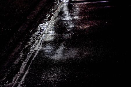 There is asphalt road after rain at night.Black and white image Фото со стока