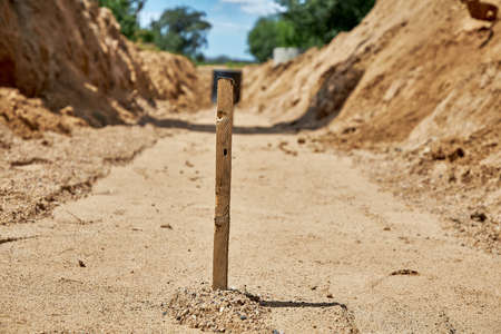 Close-up of a wooden stake for setting the height of the base of the pipeline laying in the trench, sand rammed base
