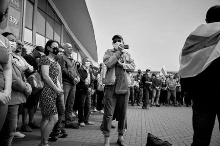 June 7 2020 Minsk Belarus A rally where a Mature man with a phone takes photos of people standing in protest 新聞圖片