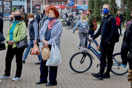 June 14 2020 Minsk Belarus An elderly woman wearing a United States colored mask stands among many masked people at a protest rally in the city square