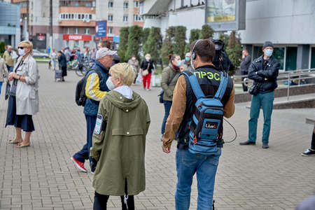 June 14 2020 Minsk Belarus A masked woman and a man with a large camera walk down the street among masked people