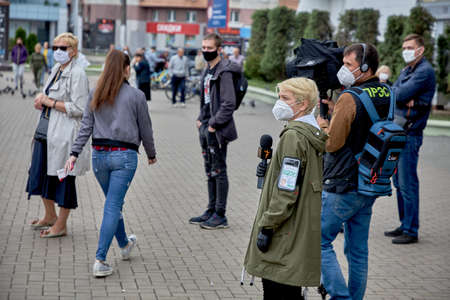 June 14 2020 Minsk Belarus Two reporters in masks walking on the street among the procession of people in masks