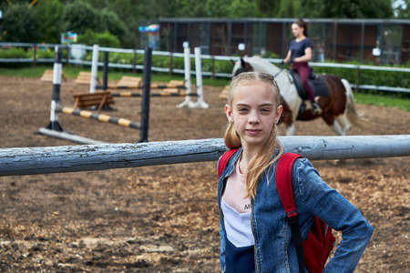 June 21 2020 Minsk Belarus A teenage girl stands next to an aviary where a girl is engaged in equestrian sports on a horse