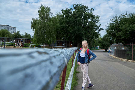 June 21 2020 Minsk Belarus A beautiful teenage girl stands next to an aviary where girls are engaged in equestrian sports on horses 新聞圖片