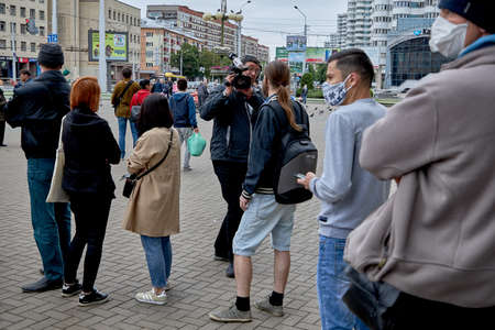 June 14 2020 Minsk Belarus A man with a backpack answers questions from a man with a large camera among walking people