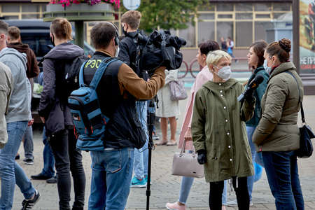 June 14 2020 Minsk Belarus A female reporter with a microphone and a man with a camera interview a masked woman at a protest rally