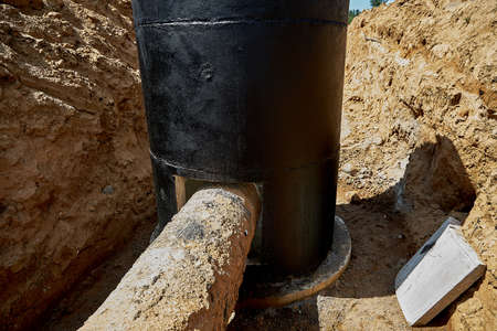 Entering an old metal water pipe into a reinforced concrete well.Reconstruction of the old water pipeline