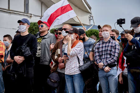 June 7 2020 Minsk Belarus People in medical masks stand at a protest rally.An opposition flag is being raised over people