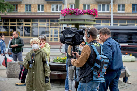 June 14 2020 Minsk Belarus A man with a large camera takes video of a female reporter with a microphone on the street