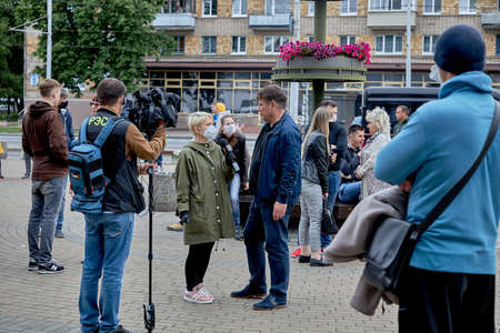June 14 2020 Minsk Belarus A masked female reporter with a microphone interviews a man on the street 新聞圖片