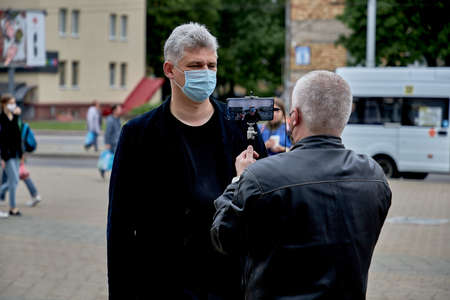 June 14 2020 Minsk Belarus There is a portrait of a masked man answering questions from a blogger who is filming it on his phone
