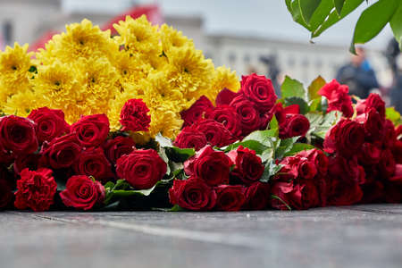 Flowers lie on the granite slab of the monument.Close up