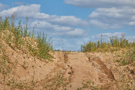 A sandy road with traces of construction equipment going up