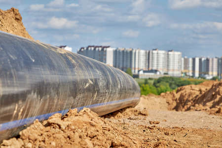 A plastic water pipe lies on the ground against the background of the city in the distance 版權商用圖片