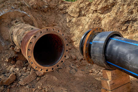 An old steel water pipe with a welded flange lies next to a new plastic pipe installed to connect the water supply system 版權商用圖片 - 163142905