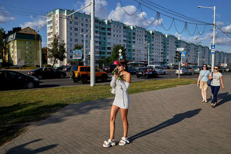August 15 2020 Minsk Belarus A young woman with a red rose talking on the phone 新聞圖片