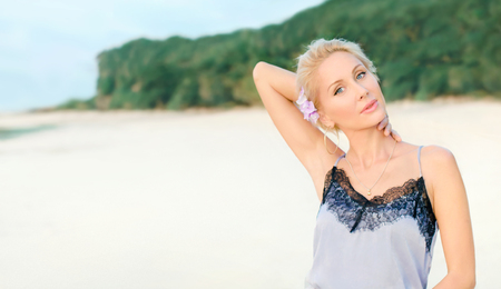 Beautiful white woman with short hair on a beach (coast) in elegant dress with black lace. Girl stand near the Ocean with one arm behind her head. Blonde slim model with blue eyes on summer vacation