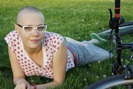 shaved head: bald woman lying on the grass  with bicycle