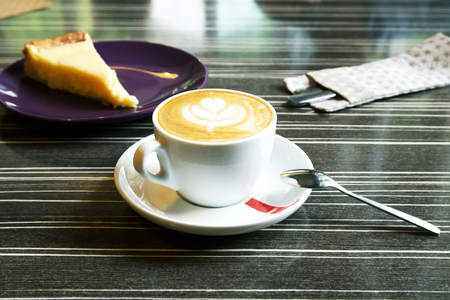 invigorate: Morning cappuccino coffee and cheesecake. Cheesecake and kitchen appliances on the background. Coffee with art foam.