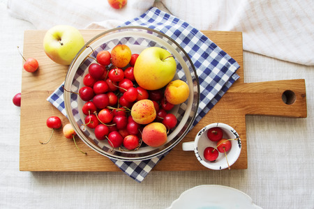 longevity: Composition of fruits and berries. Reason for the longevity is apples, cherries, apricots. Fruits and berries in a bowl on a checkered napkin on the table. Fruits and berries on a wooden cutting board Stock Photo