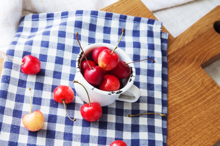 longevity: Composition of cup and berries. Cherries is the reason of the longevity . White retro cup and berries on a checkered napkin on the table. Retro cup and berries on a wooden cutting board Stock Photo